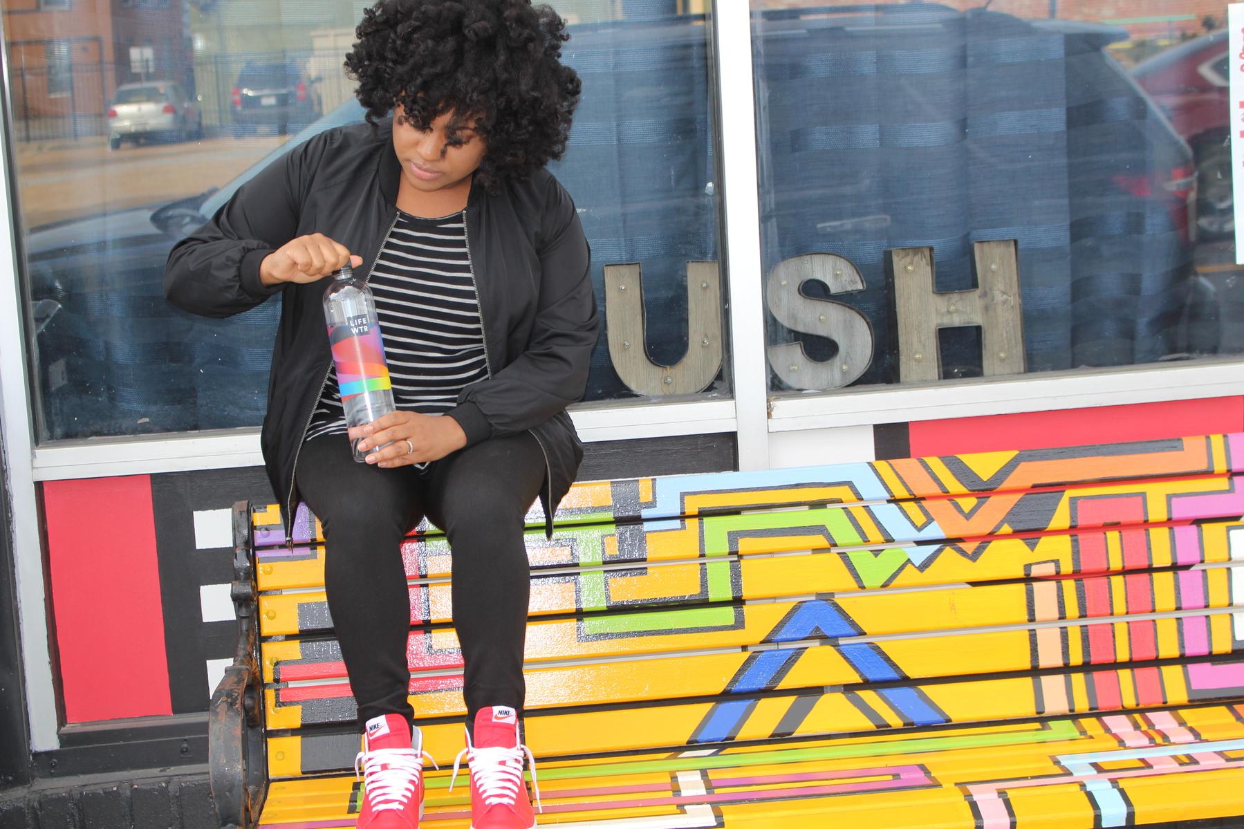 sitting on bench holding LIFEWTR