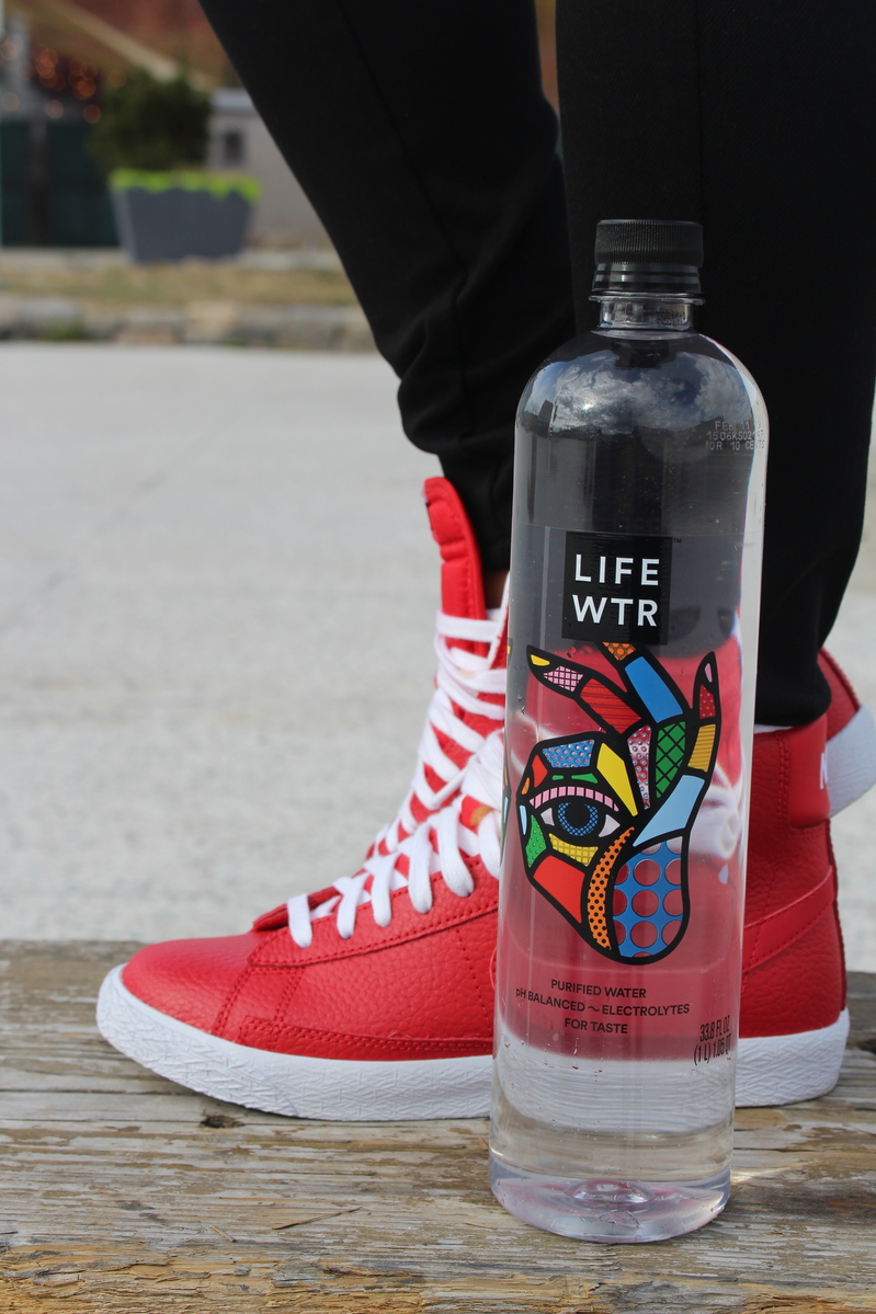 holding LIFEWTR, red sneakers