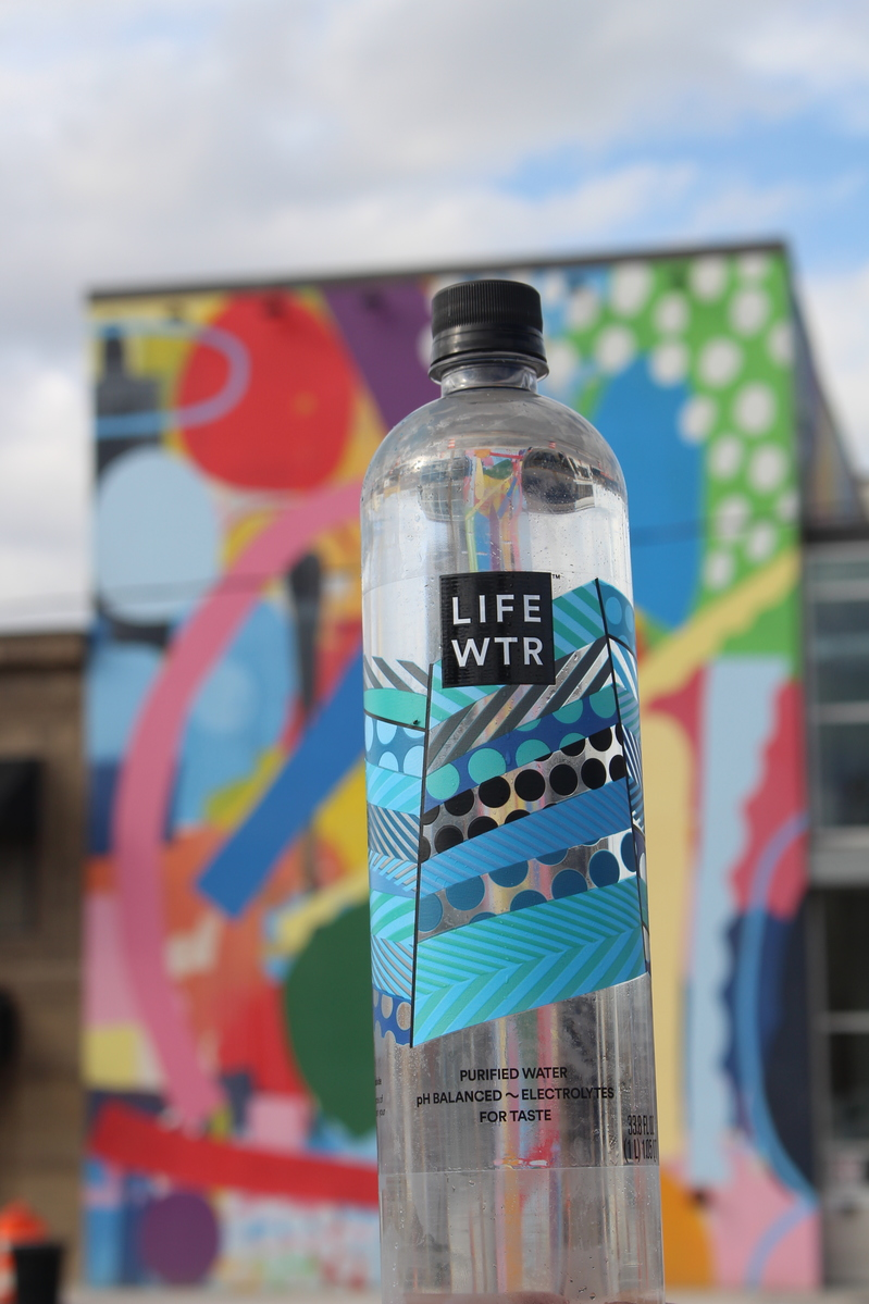 LIFEWTR bottle with mural in background
